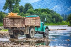 Old truck transports cargo wade across the river. Old dirty truck royalty free stock photo