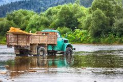 Old truck transports cargo wade across the river. Old dirty truck stock photo