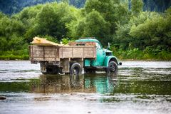 Old truck transports cargo wade across the river. Old dirty truck stock photos