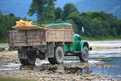 Old truck transports cargo wade across the river Royalty Free Stock Image