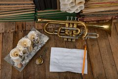 Old trumpet covered with patina on an old wooden table. Musical instrument and old books stock photography