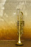 Old Trumpet. Old worn trumpet stands alone against a grungy wall outside a jazz club stock image