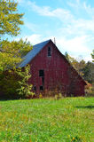 Old tumbledown red barn. Near woods on an early fall day Stock Photography