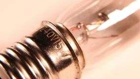 Old tungsten bulb with filament. Macro shot of a classic tungsten bulb and filament stock footage