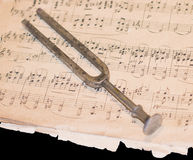 Old tuning fork on the dilapidated notes Stock Image