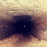Old tunnel, moistened walls. Dry channel carved in sandstone rock Stock Photos