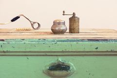 Old Turkish manual grinder, immersion heater and wheat. On a wooden table Stock Photo
