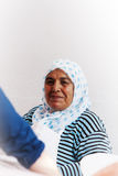 Old turkish woman smiling. An old turkish woman, wearing traditional white scarf with blue points, is smiling nicely while sitting near a white wall, and Royalty Free Stock Photos