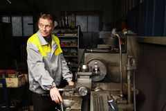 Old turner is standing near the lathe. stock image