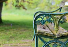 Old turquoise blue painted cast iron garden bench. With weathered wooden planks, blurred green background stock photo