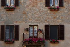 Old tuscany balcony with geranium flowers in the small magical and old village of Pienza, Val D`Orcia Tuscany – Italy Royalty Free Stock Photography
