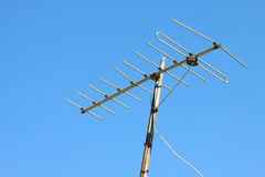 Old TV antenna on house roof with blue sky. Royalty Free Stock Image