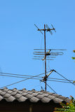 Old TV antenna on house roof with blue sky. Stock Photos