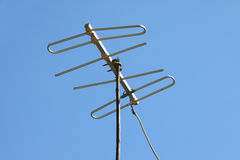 Old TV antenna on house roof with blue sky. Royalty Free Stock Photography