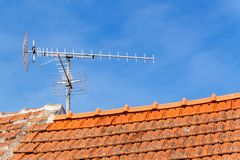 Old TV antenna on red roof. Receiving TV. Old technology communication.  royalty free stock images
