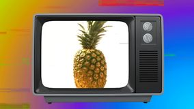 Old TV with pineapple on the screen against colorful background. Digital animation of an old TV with a pineapple on the screen against a colored blurring in the stock video footage