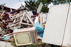 Old TV set and fridge on the dump. Junk yard dump with focus on old TV and fridge Stock Photo