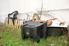 Old TV set and the rest of bulky trash. Old TV thrown away next to a wall with a pile of mixed garbage. Stock Image
