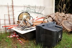 Old TV set and the rest of bulky trash. Old TV thrown away next to a wall with a pile of mixed garbage. In natural environment. Recycling industry. Not Ecology Royalty Free Stock Photo