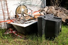 Old TV set and the rest of bulky trash. Old TV thrown away next to a wall with a pile of mixed garbage. In natural environment. Recycling industry. Not Ecology Royalty Free Stock Image