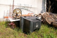 Old TV set and the rest of bulky trash. Old TV thrown away next to a wall with a pile of mixed garbage. Stock Images