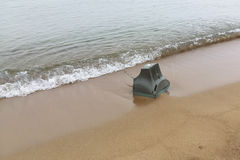Old TV on the shore of sea. Old TV thrown on the sea shore royalty free stock photos