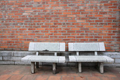 Old twin chairs near grungy red brick wall Stock Image