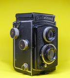 Old Twin Lens Camera. An old twin lens Rolleicord camera on yellow background. An antique analog camera royalty free stock photos
