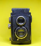 Old Twin Lens Camera. An old twin lens Rolleicord camera on yellow background. An antique analog camera stock photography
