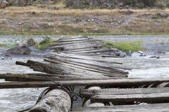 Old twisty bridge across river. Unsafe looking narrow old twisted bridge across river stock photos