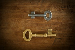 Old two keys placed on a wooden floor loe key light. Royalty Free Stock Image