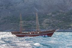 Old two-masted yacht in the sea against rocky shore. Old two-masted yacht in stormy sea against rocky shore Stock Photo