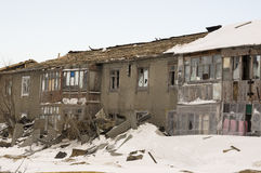 Old two-storied destroyed house in winter with snow around. Poverty and misery, North Stock Photos
