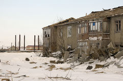 Old two-storied destroyed house in winter with snow around. Poverty and misery, North Stock Photography