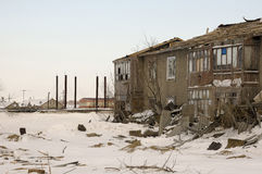 Old two-storied destroyed house in winter with snow around. Poverty and misery, North Royalty Free Stock Photos