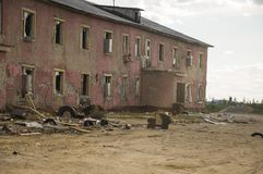 Old two-storied destroyed red house in autumn with sand around. Poverty and misery, North.  Stock Images