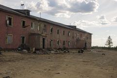 Old two-storied destroyed red house in autumn with sand around. Poverty and misery, North.  Royalty Free Stock Photos