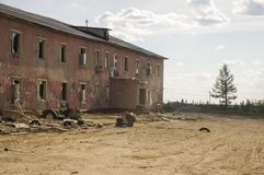 Old two-storied destroyed red house in autumn with sand around. Poverty and misery, North.  Stock Photo