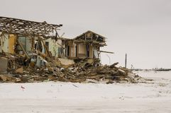 Old two-storied destroyed, ruined and desolated house in winter with snow around. Poverty and misery, North.  Royalty Free Stock Images