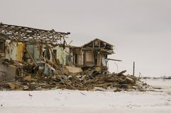 Old two-storied destroyed, ruined and desolated house in winter with snow around. Poverty and misery, North.  Royalty Free Stock Photography
