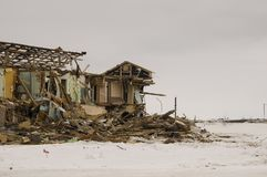 Old two-storied destroyed, ruined and desolated house in winter with snow around. Poverty and misery, North.  Stock Photo