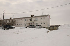 Old two-storied  house in winter with snow, cars and trees on the yard. Poverty and misery, North Royalty Free Stock Photos