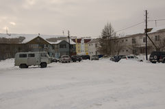 Old two-storied  house in winter with snow, cars and trees on the yard. Poverty and misery, North Stock Photography