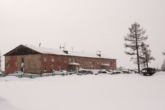Old two-storied  red house in winter with snow, cars and trees on the yard. Poverty and misery, North Royalty Free Stock Images