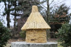 Old type beehive made of strew on a millstone. royalty free stock photo