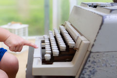 Old typewriter and baby hand Stock Photo