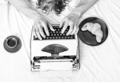 Old typewriter on bedclothes. Male hands type story or report using vintage typewriter equipment. Writing routine. No. Day without chapter. Vintage typewriter royalty free stock images