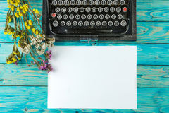 Old typewriter and a blank sheet of paper. Retouching author writer. Blue wooden table dry flowers. Top view. The creative process of writing a new novel stock photos