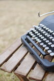 Old Typewriter with Copy Space. An old typewriter sits on a wooden table evoking writers and creativity in the warm outdoors Royalty Free Stock Image