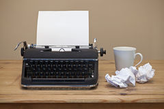 Old typewriter on a desk. An old retro typewriter with a piece of blank paper for you to add your own text, coffee mug and two pieces of screwed up paper besides Stock Photo